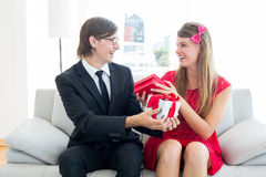 Cute geeky couple smiling and offering gift Royalty Free Stock Photos