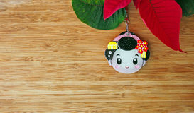 Cute  geisha face and poinsettia flower on wooden background Stock Photography
