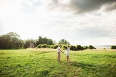 Cute gentle couple walking in the green meadow. Young loving family enjoying spring time.  stock photography