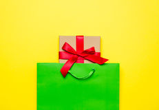 Cute gift in beautiful green shopping bag on wonderful yellow ba Royalty Free Stock Photography