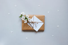 Cute gift box with craft paper and flowers top view. Mother`s and woman`s day concept stock photos