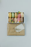 Cute gift box with delicious colorful macaroons on the light blue background, top view Stock Photos
