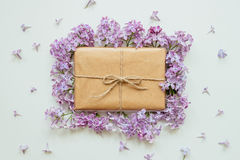 Cute gift box wrapped with craft paper and lilac flowers top view. Gift for any holiday Royalty Free Stock Photography