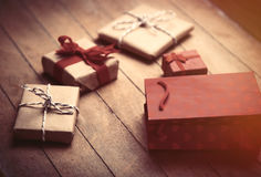 Cute gifts and cool red shopping bag on the wonderful brown wood Royalty Free Stock Image