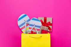 Cute gifts and cool sandals in shopping bag and cool laptop on w Stock Image