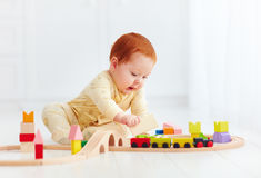 Cute ginger baby playing with toy railway road at home Royalty Free Stock Images