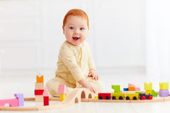 Cute ginger baby playing with toy railway road at home Stock Photo