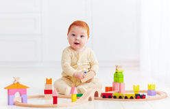 Cute ginger baby playing with toy railway road at home Stock Photos