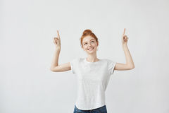 Cute ginger girl with freckles smiling pointing fingers up. Stock Images