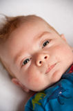 Cute ginger haired baby lying down. Close up image of a ginger haired adorable baby boy with the focus being on his piercing blue eyes. He is wearing a patterned stock photos