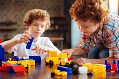 Cute ginger haired boy building car on table. Building a dream car. Selective focus on an adorable child looking at a colorful built automobile while sitting on Stock Images