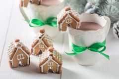 Cute gingerbread cottages with sweet drink in Christmas winter evening Stock Photos