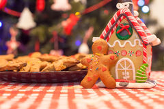 Cute gingerbread man and candy ginger house. Cute gingerbread man in front of his candy ginger house background the Christmas tree lights royalty free stock photo