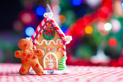 Cute gingerbread man and candy ginger house. Cute gingerbread man in front of his candy ginger house background the Christmas tree lights stock photos