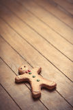 Cute gingerbread man lying on the wonderful brown wooden backgro Royalty Free Stock Photography