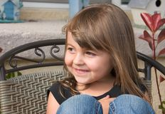 Cute girl. A cute young girl smiles while sitting in a chair royalty free stock photography