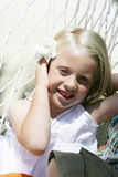 Cute Girl. A portrait of a cute smiling girl with a white flower resting on a hammock Stock Photos