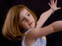 Cute girl. Cute little red-headed girl stretching on dark background Stock Images