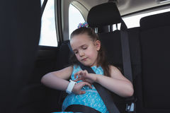 Cute girl adjusting smart watch. In car Royalty Free Stock Image