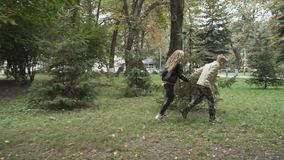 Cute girl and adorable boy holds hands and running in park in slowmotion stock video footage