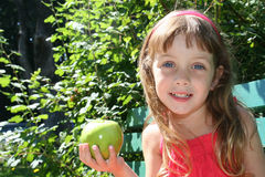 Cute girl with apple. Portrait of cute young girl with green apple outdoors; leafy background Stock Photography