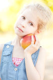 Cute girl with apple. Cute kid girl holding fresh apple outdoors Stock Photo