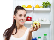 Cute girl with apple near the open refrigerator Stock Photography