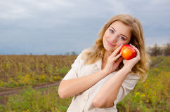 Cute girl with apple. Cute smiling girl holding an apple in her hands Royalty Free Stock Image