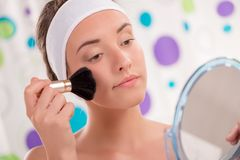 Cute Girl Applying Blush. Close-up of beautiful young woman applying blush in front of mirror in his bathroom in the morning Royalty Free Stock Photography