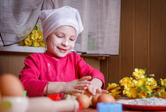 Cute girl in apron rolling dough Stock Photography