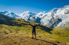 Cute girl with arms wide open, wearing  coat, standing in front. Woman with arms wide open standing in front of Monte rosa glacier Stock Image