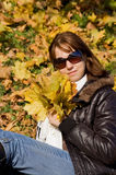 Cute girl with autumn leaves Stock Photos