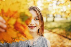 Cute girl in a autumn park. Pretty cute girl with make up, dressed in black dress standing in a autumn park keeps the leaves near the face stock photo
