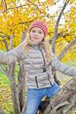 Cute girl in autumn sit on tree Royalty Free Stock Photo