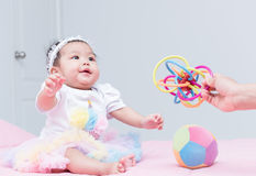 Cute girl baby smile and play toy with mother hand Stock Images