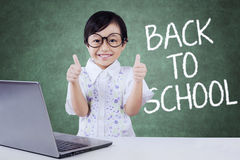 Cute girl back to school and shows thumb up Stock Photo