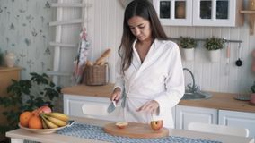 Cute girl in bathrobe takes apple, puts it on board, cuts it in kitchen, slow motion. Cute brunette girl in white bathrobe takes apple, puts it on board and cuts stock footage
