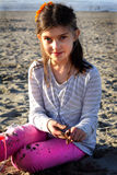 Cute Girl at Beach. A cute little 9 year old girl in a striped blouse and pink pants with brown hair playing in the sand at the beach. Shallow depth of field Stock Photo