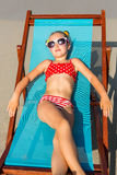 Cute girl on the beach. Cute little girl in red swimsuit and sunglasses enjoying on a sun lounger rest on the beach chair on tropical sandy beach sea shore Stock Image