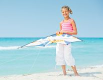 Cute girl on beach playing with a colorful kite Royalty Free Stock Image