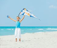 Cute girl on beach playing with a colorful kite Royalty Free Stock Photos