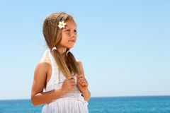 Cute girl on beach staring. Cute girl in white dress with staring face expression Stock Photo