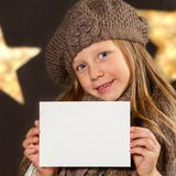Cute girl with beanie holding white card. Stock Photography