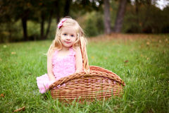 Cute girl in a beautiful dress in a basket in a summer pa Stock Photo