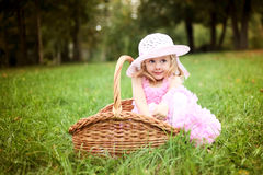 Cute girl in a beautiful dress in a basket in a summer pa Stock Photos
