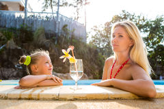 Cute girl and beautiful mother at the pool. Outdoor portrait of beautiful blonde mother and her cute daughter. Little girl look to her mother at the pool. Big Royalty Free Stock Photos