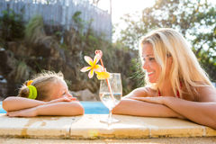 Cute girl and beautiful mother at the pool. Outdoor portrait of beautiful blonde mother and her cute daughter. Little girl look to her mammy at the pool. Big Stock Image