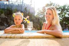 Cute girl and beautiful mother at the pool Royalty Free Stock Images