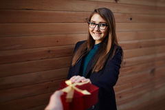 Cute girl with a beautiful smile reaches for gift Royalty Free Stock Photo