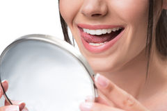 Cute girl with beautiful toothy smile. Close up of cheerful young woman touching her white clean teeth by tongue with enjoyment. She is holding mirror and Royalty Free Stock Photography